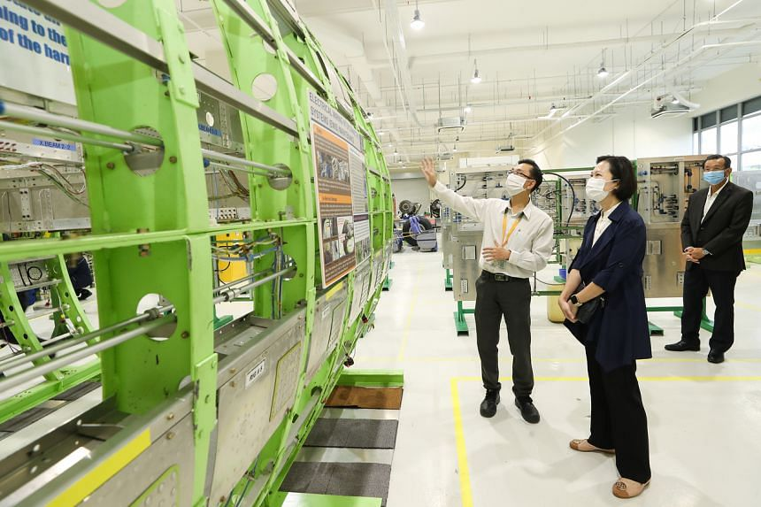 Lean Academy instructor Colin Foo (left) explaining to Minister of State Gan Siow Huang how training is conducted using a scaled-down aircraft fuselage replica, at the academy on Sept 7, 2021.