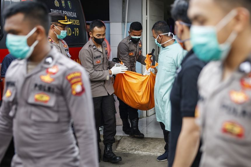 Police officers carry a body bag in the aftermath of a prison fire, at a hospital in Tangerang, Banten, Indonesia on Sept 8, 2021.