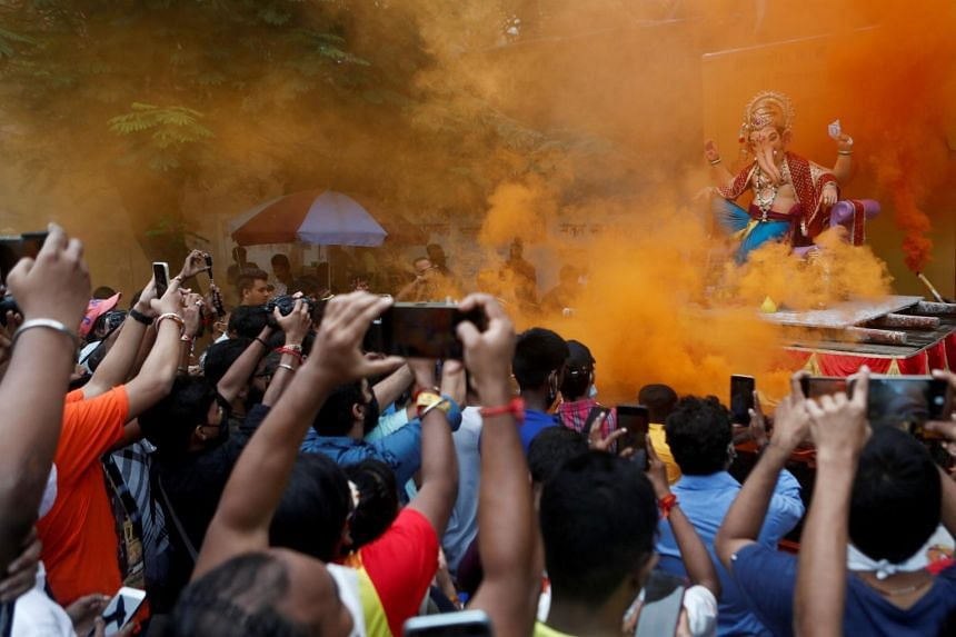 Devotees flocking to catch a glimpse of an idol of the Hindu god Ganesh as it leaves a workshop in Mumbai on Sept 5, 2021.