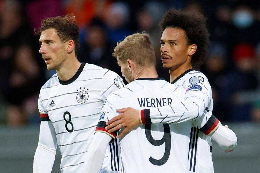 Forward Leroy Sane (right) celebrates with teammates Timo Werner and Leon Goretzka after scoring Germany's third goal.