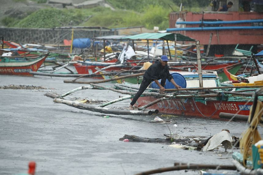 A fisherman securing a boat at a coastal village in Bacoor, in the Philippine province of Cavite, on Sept 8, 2021.
