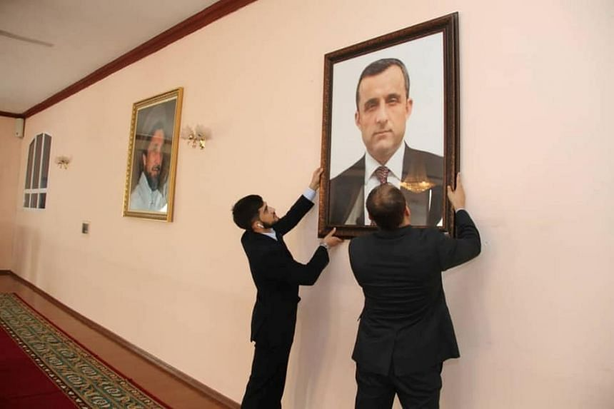 Afghan embassy staff hanging a portrait of former Afghan first vice-president Amrullah Saleh at the embassy in Tajikistan, in August 2021.