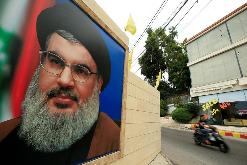 A man riding his motorbike past a picture of Lebanon's Hizbollah leader Sayyed Hassan Nasrallah.