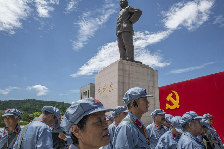 Tourists in Red Army garb visit a statue of Mao in Yan'an, in China's Shaanxi province on June 18, 2021.