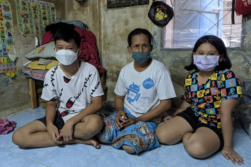 Student Peerapat Tiemkoksung, seen here with his mother Somporn Boonnoi and sister Pornphan, has found remote learning to be a challenge, especially because his family used to own only one mobile device.