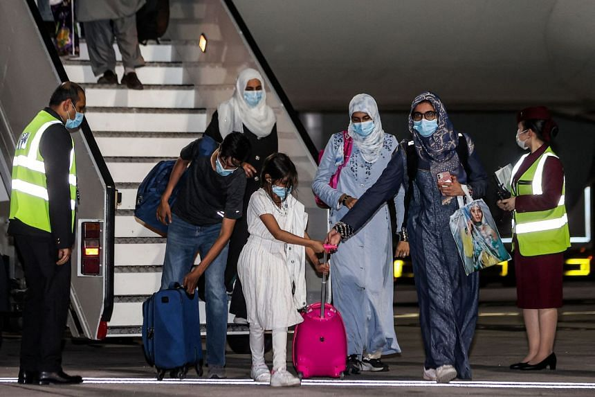 Evacuees from Afghanistan arrive at Hamad International Airport in Qatar's capital Doha on the first flight carrying foreigners out of the Afghan capital since the conclusion of the US withdrawal.