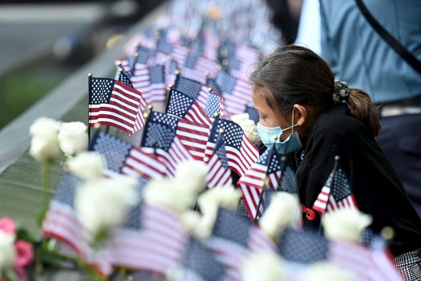 A family member places a flag at the reflecting pool in New York, on the 20th anniversary of 9/11.