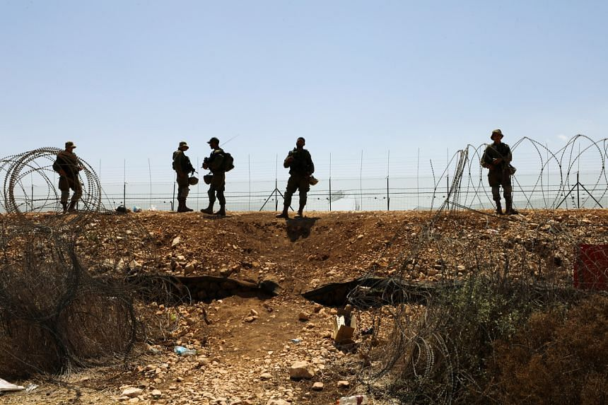 Israeli soldiers guard along a fence as part of search efforts to capture six Palestinian men who had escaped from prison earlier this week.