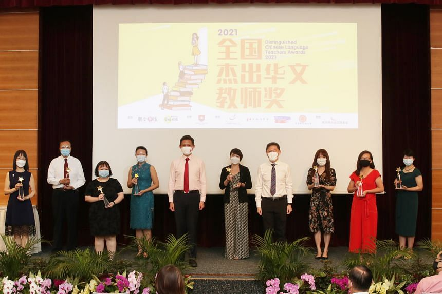 Education Minister Chan Chun Sing (fifth from left) and SPH deputy CEO Anthony Tan (fourth from right) with the eight teachers at the awards ceremony.