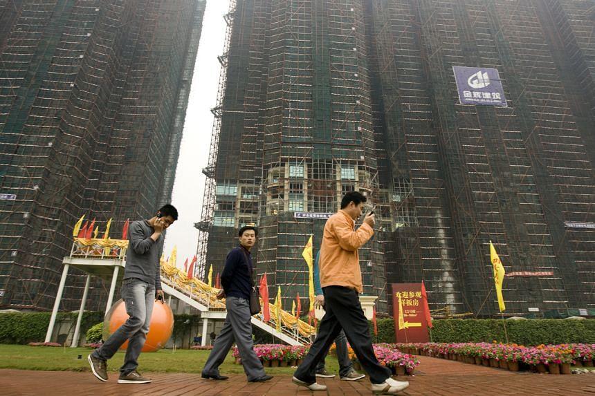 Prospective investors walk around the Royal Scenic Peninsula, an Evergrande luxury development in Guangzhou on March 27, 2009.