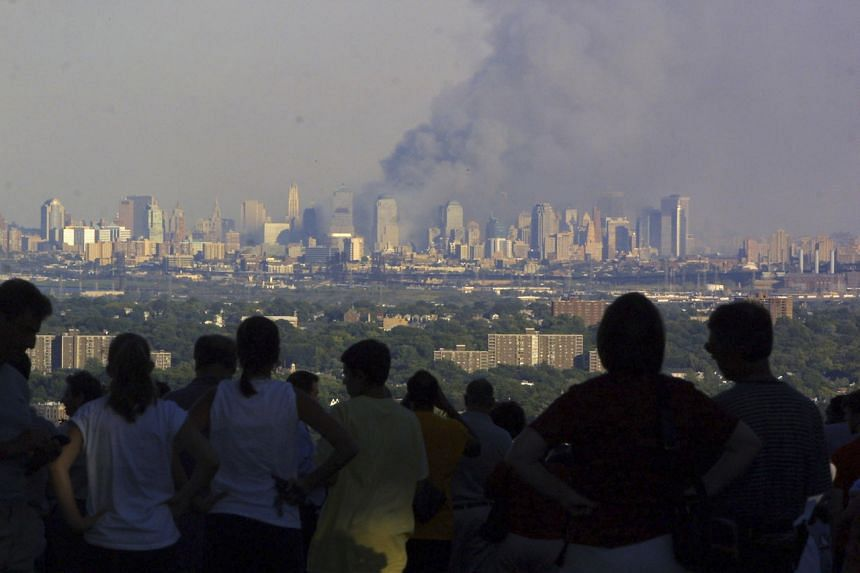 People watch smoke rise from the World Trade Center at the park in Eagle Rock Reservation, New Jersey, on Sept 11, 2001.