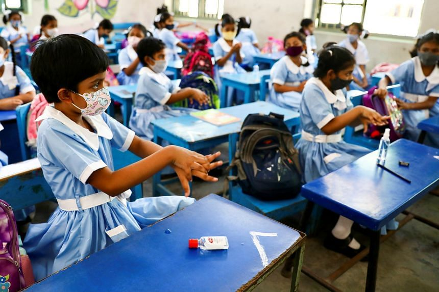In Dhaka, students at one school were welcomed with flowers and sweets, and told to wear masks and sanitise their hands.