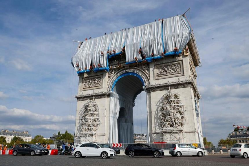 Workers were shuffling around the 19th century arch setting up 25,000 square metres of  recyclable plastic wrapping.