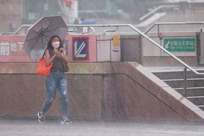 A woman walks in strong wind and rain caused by Typhoon Chanthu in Taipei, on Sept 12, 2021.
