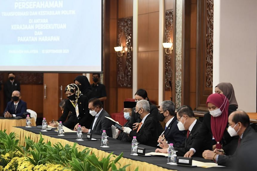 Malaysian Prime Minister Ismail Sabri Yaakob (seated, fourth from right) inking the cooperation deal with Pakatan Harapan on Sept 13, 2021.