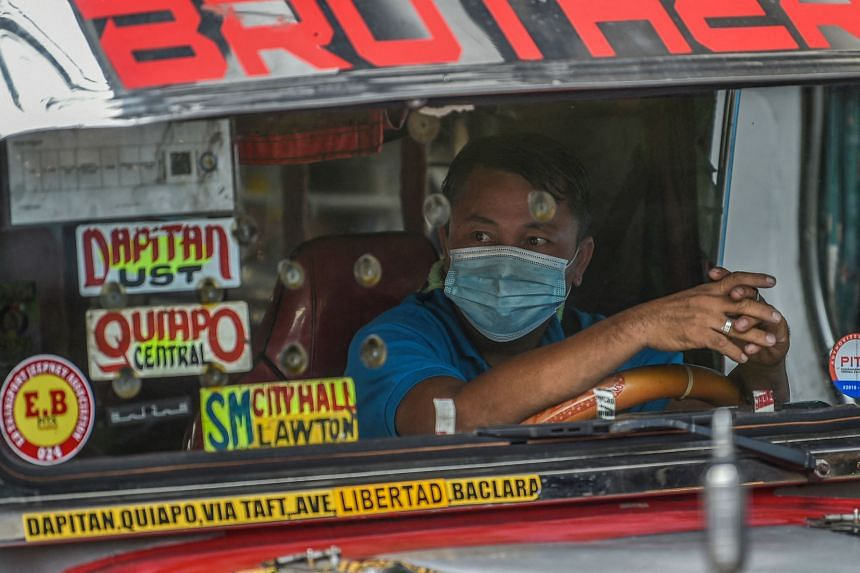 A jeepney driver wearing a face mask to protect himself against the Covid-19 coronavirus drives along a street in Manila on Sept 7, 2021.