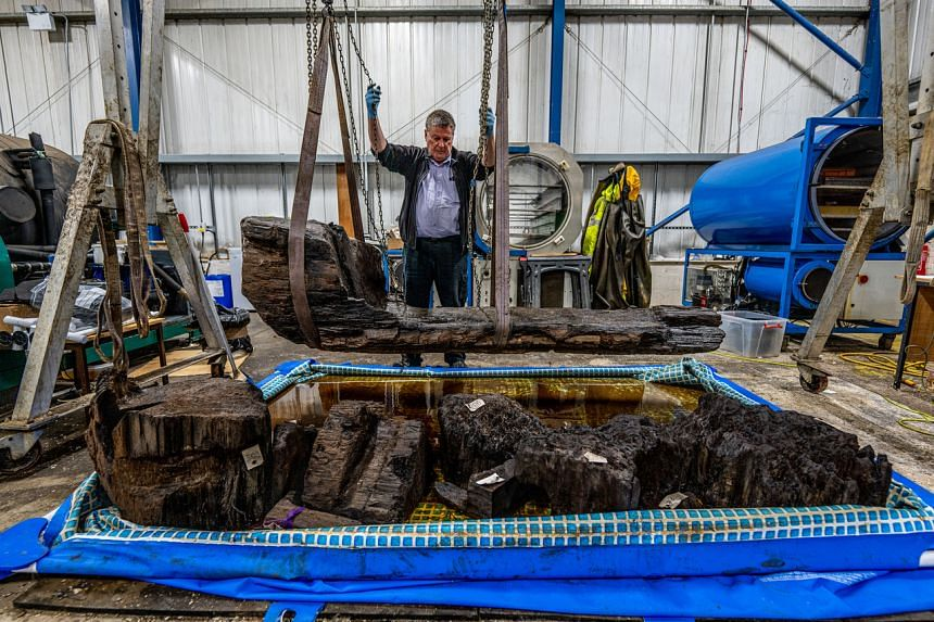 York Archaeological Trust conservation head Ian Panter with the Bronze Age log coffin discovered on a British golf course in 2018.