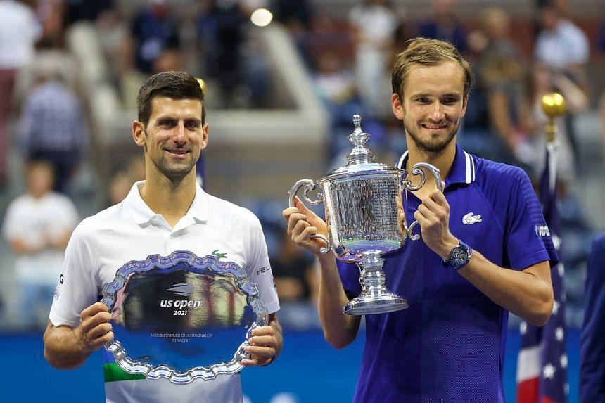 Novak Djokovic (left) holds the runner-up trophy alongside Daniil Medvedev who celebrates with the championship trophy after winning the US Open on Sept 12, 2021.