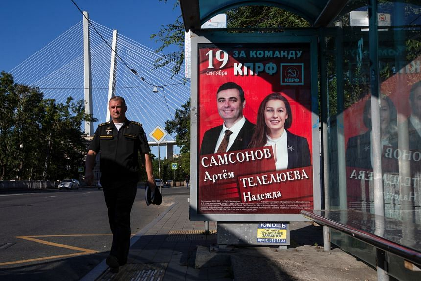 A man walks past a campaign poster of Communist Party candidates ahead of a parliamentary election in Vladivostok, on Sept 12, 2021.