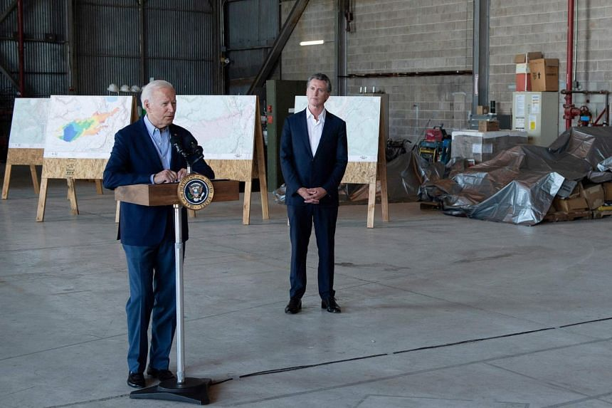 Mr Joe Biden speaks about wildfires and climate change as Mr Gavin Newsom listens at Sacramento Mather Airport on Sept 13, 2021.