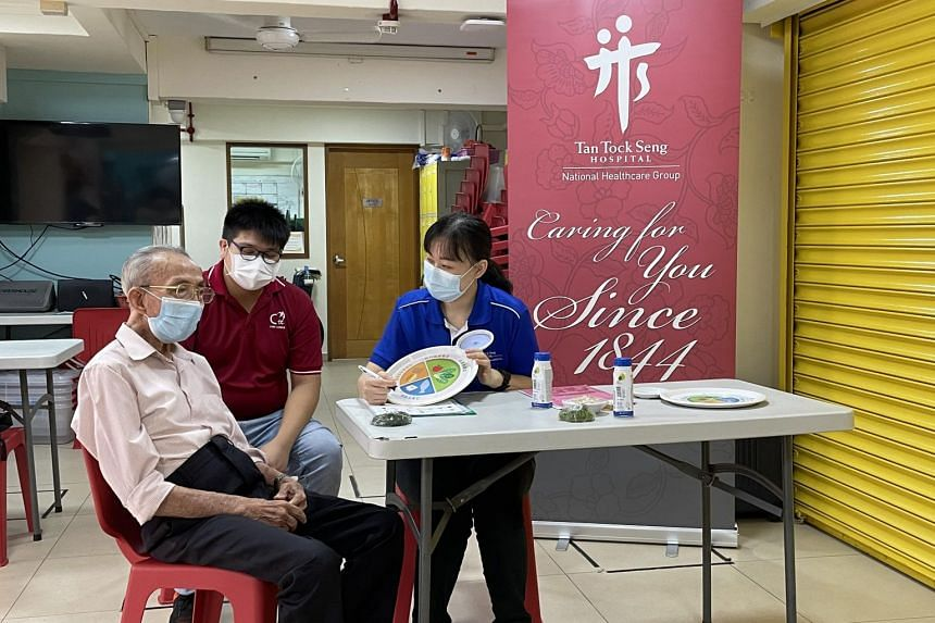 TTSH senior community dietitian Chng Pey Ling (right) expalning nutritious foods to Mr Lim Ngak Boon.