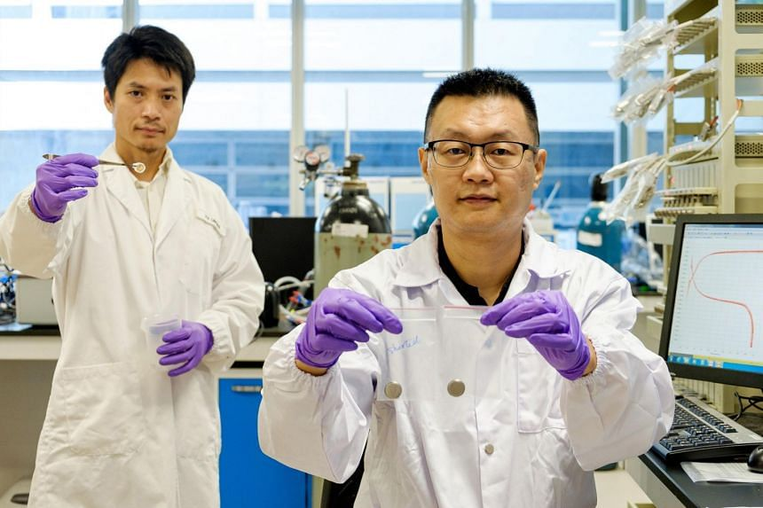 Prof Jason Xu (right) holding a short-circuited battery in his right hand, and a Li-ion battery which uses the new NTU Anti-short Layer technology. Dr Yu Linghui is holding the anti-short layer applied on a battery separator.