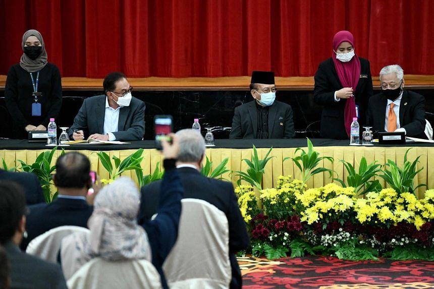 Malaysian Prime Minister Ismail Sabri Yaakob (right) and Pakatan Harapan leader Anwar Ibrahim (left) signing the bipartisan deal on Sept 13, 2021.
