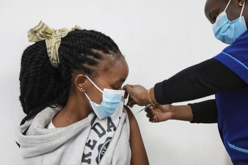 A medical staff members administers a first dose of the Moderna Covid-19 vaccine to a woman during a vaccination drive in Nairobi, Kenya.