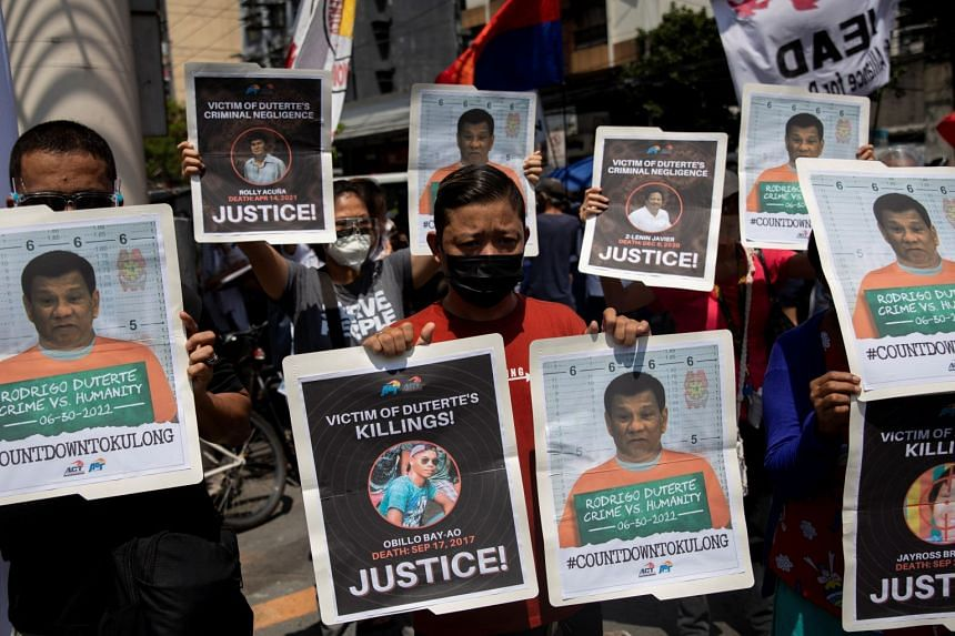Protesters hold photographs of alleged victims of extra-judicial killings and mock mugshots of President Rodrigo Duterte, during a protest to mark Duterte's final year in office, in Manila, in June 2021.