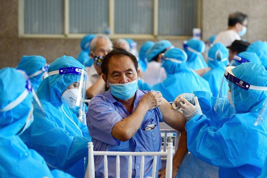 A man (centre) receives the AstraZeneca Covid-19 coronavirus vaccine in Hanoi on Sept 10, 2021.