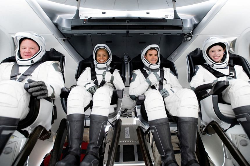 The quartet of amateur space travellers are strapped into the pressurised cabin of the Crew Dragon capsule.
