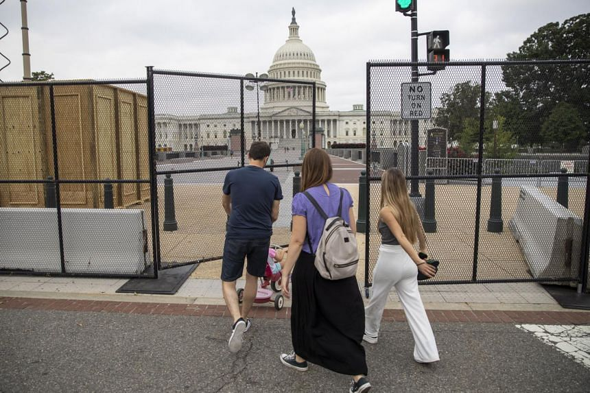 Pedestrians navigate temporary security fencing around the US Capitol in Washington, DC, on Sept 16, 2021.