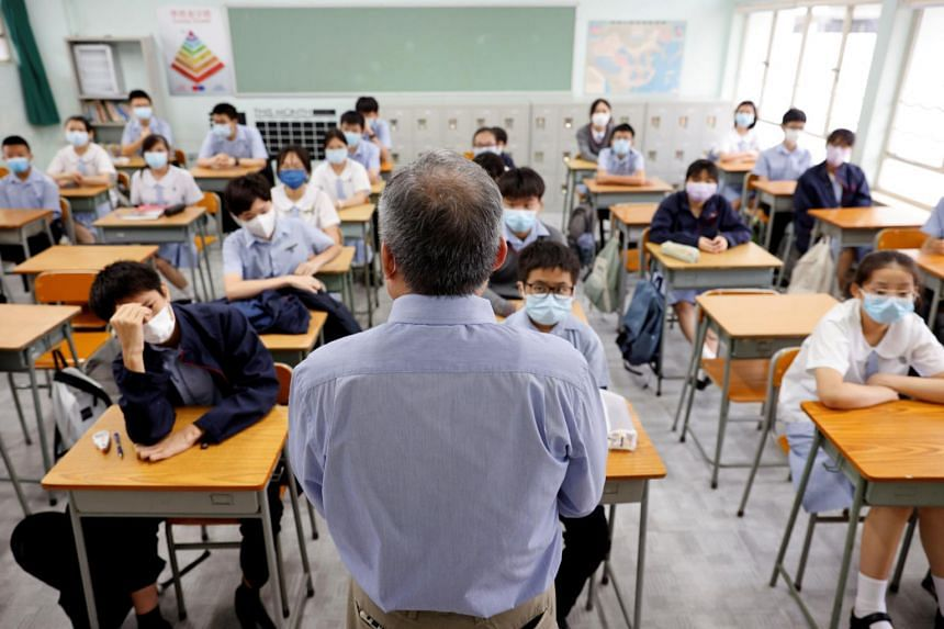 A teacher introduces himself to students on the first day of the new term at a secondary school in Hong Kong on Sept 1, 2021.