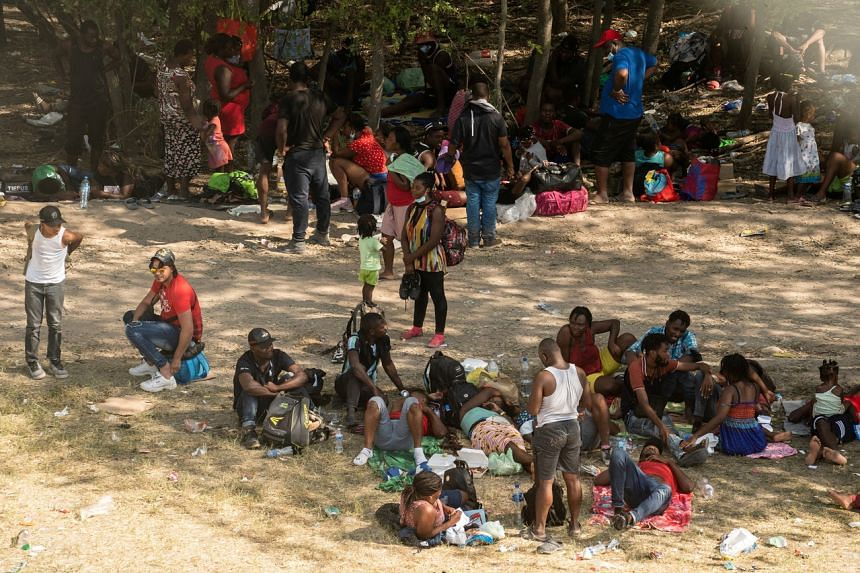 Asylum-seeking migrants rest under shade near the International Bridge between Mexico and the US in Del Rio, Texas, on Sept 15, 2021.