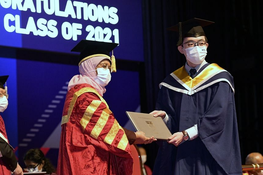 Lee Kuan Yew gold medal award recipient Gerald Sim (right) receives his award from President Halimah Yacob, on Sept 17, 2021.