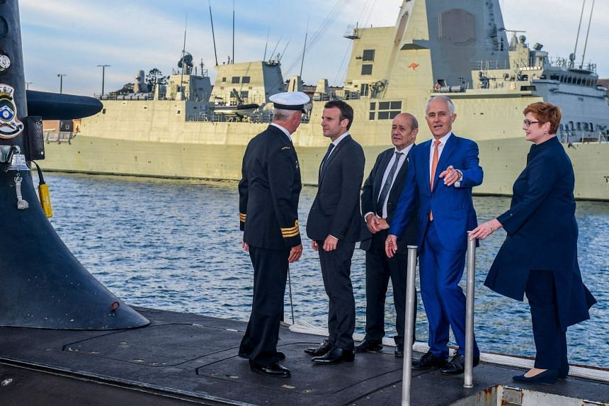 French President Emmanuel Macron (second from left) and Australian Prime Minister Malcolm Turnbull (second from right) standing on the deck of a Royal Australian Navy submarine in Sydney in 2018.