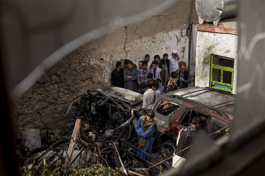 Relatives and neighbours gather near damage from a US drone strike in the courtyard of Zemari Ahmadi's home in Kabul, Afghanistan, on Aug 30, 2021.