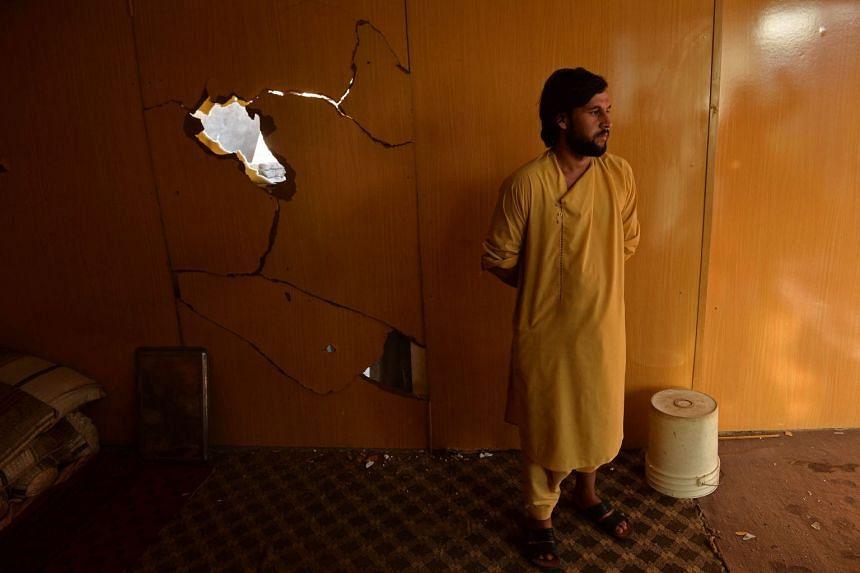 Farshad Haidari, nephew of Ezmarai Ahmadi, stands next to a wall of Ahmadi's house that was damaged in a US drone strike.