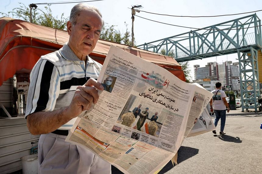 """An Iranian man reads a copy of the daily newspaper Etalaat, bearing the headline """"Iran is a new member of the Shanghai Cooperation Organisation"""", at a kiosk in the capital Tehran, on Sept 18, 2021."""