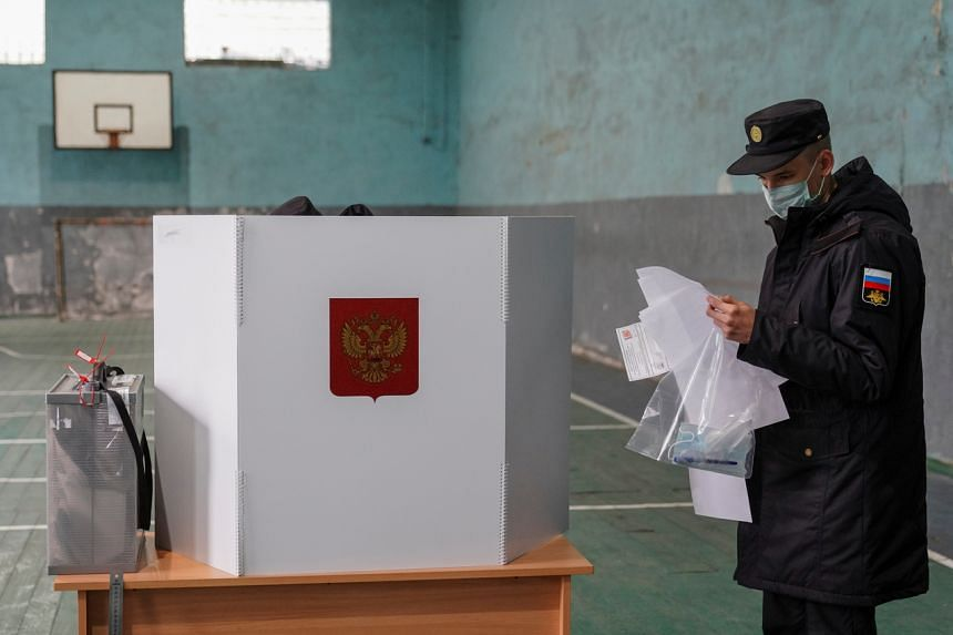 A Russian serviceman studying ballots at a polling station during a parliamentary election in Kaliningrad, on Sept 18, 2021.