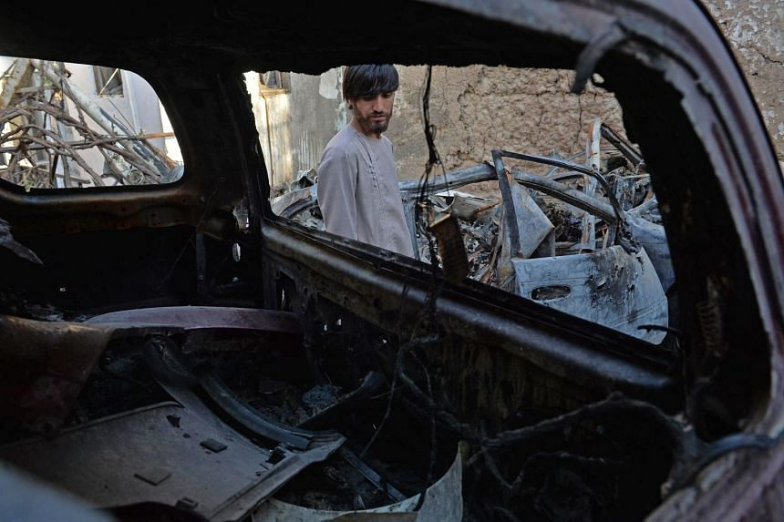 A relative of Ezmarai Ahmadi is pictured through the wreckage of a vehicle that was damaged in a US drone strike.
