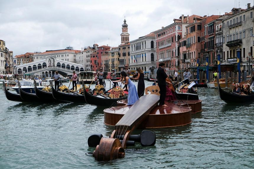 """A string quartet plays atop an enormous motorised watercraft """"Noah's Violin"""" along the Grand Canal of Venice on Sept 18, 2021."""