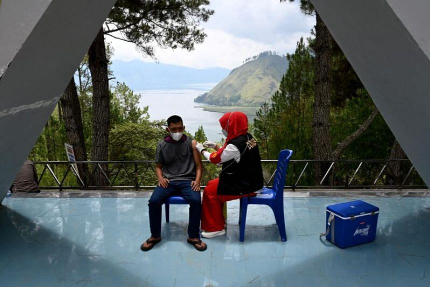 A man receives the Sinovac Covid-19 vaccine at Bur Telege, a popular spot for tourists overlooking Laut Tawar lake in Takengon, Aceh province on Sept 19, 2021.