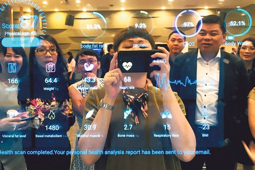 Income employees at a company-wide innovation showcase exploring different Insurtech applications, including AI for health underwriting. PHOTO (TAKEN BEFORE COVID-19): NTUC INCOME