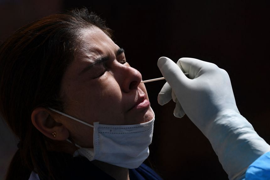 A health worker takes a nasal swab sample from a woman at a testing center in Srinagar,on Sept 15, 2021.