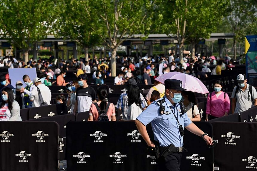 People queue to enter the Universal Studios Beijing theme park during an invitation-only test run in Beijing on Sept 1, 2021.