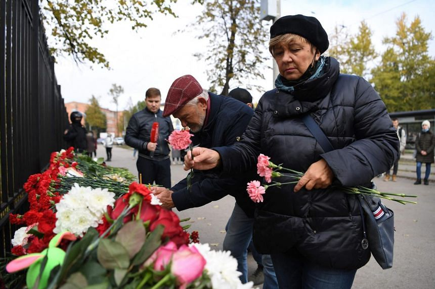 People lay flowers at the entrance of the university campus in Perm, Russia, on Sept 21, 2021.