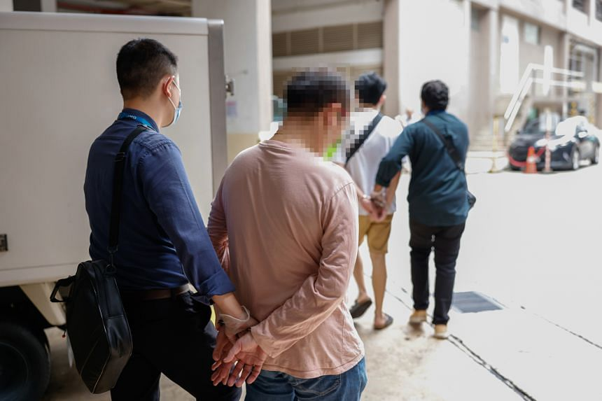 MOM officers escorting individuals suspected of being involved in illegal labour importation after their arrest. The enforcement operation took place at 22 locations around the island.