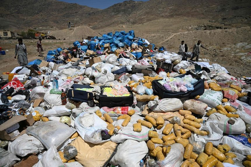 A file photo taken on July 1 shows workers and security forces preparing to set on fire a pile of seized narcotics in Kabul.
