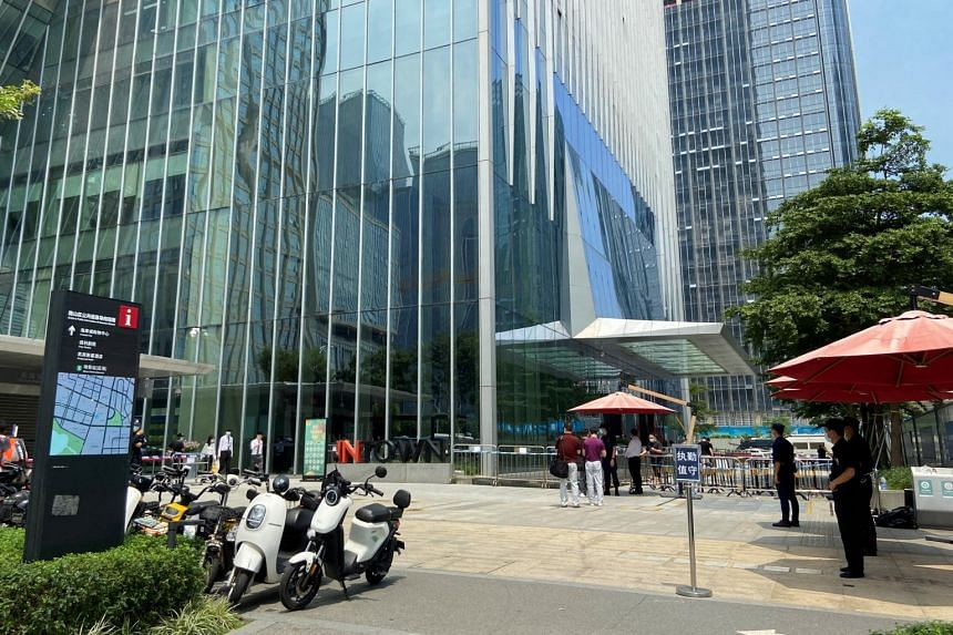 Security personnel stand guard outside Evergrande's headquarters, in Shenzhen, China on Sept 17, 2021.